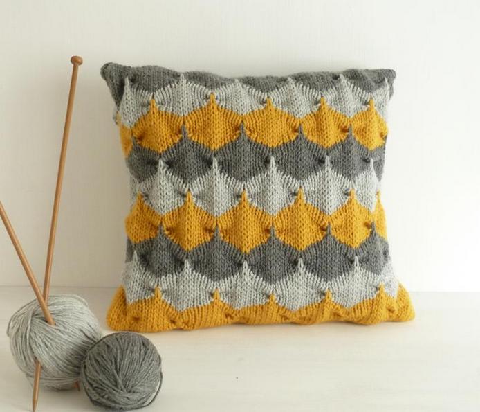 Geometric Patterned Knit Pillow Sitting Next to Knitting Needles