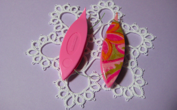 Two Pink Tatting Shuttles Laying on Lace