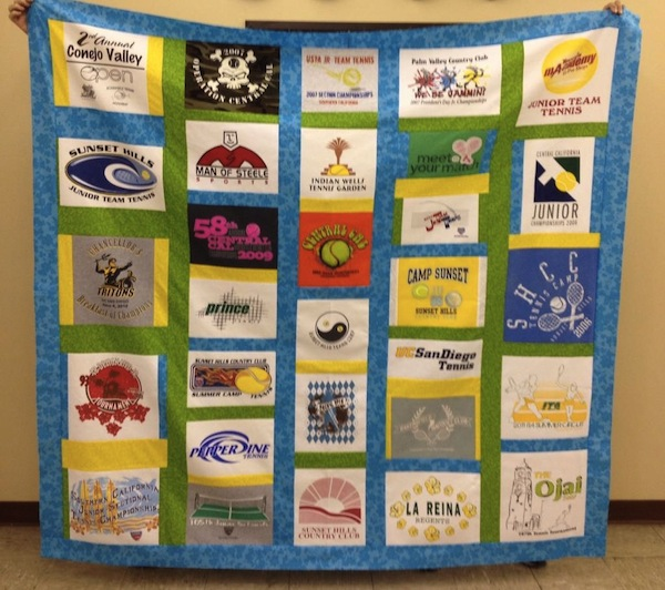 Woman Holding Up Quilt Featuring Multitudes of Logos