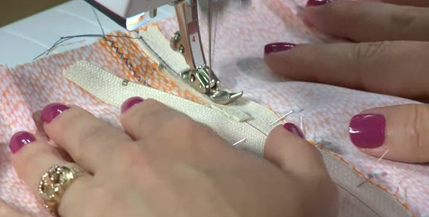 Woman's Hands Sewing Zipper into Gament