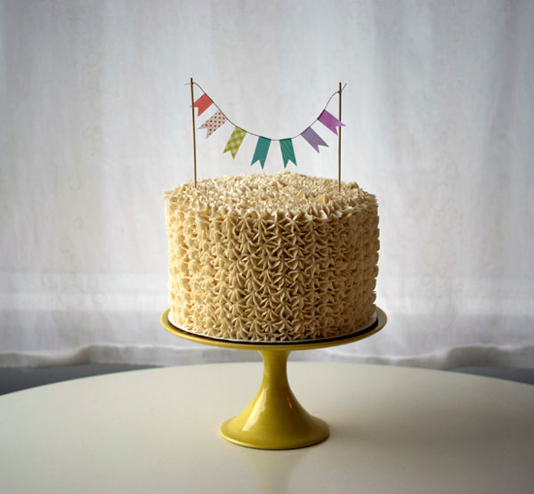 Photo of Cake with Yellow Piping and Mini Flag Garland Topper