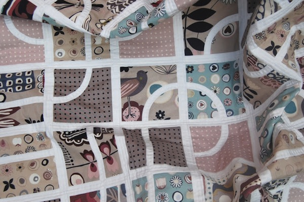 Pale Pink-Hued Quilt with White Curved Lines
