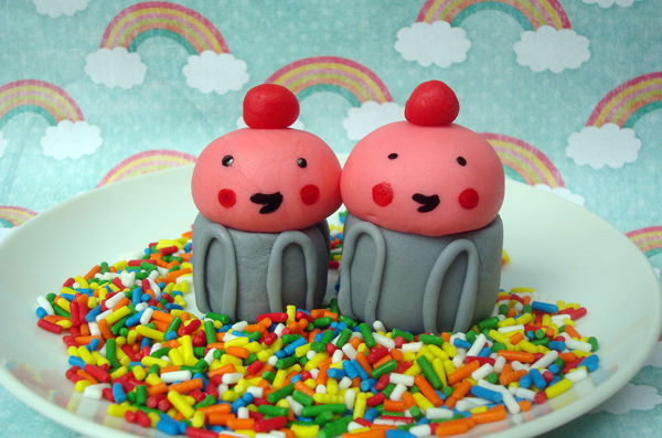 Two Cute Fondant Cupcake Figures Sitting on Sprinkles