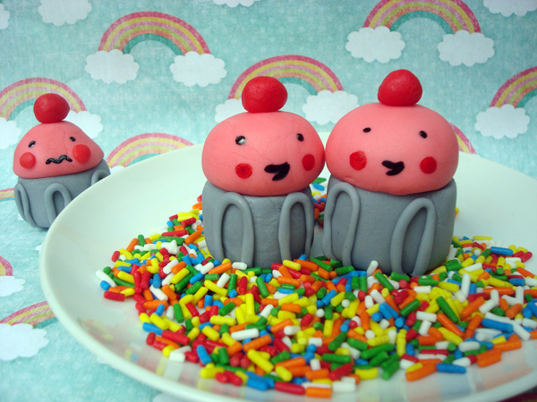 Two Happy Cupcake Fondant Figures on Sprinkles, Sad Figure in Background