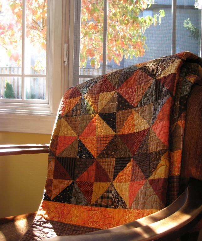 Fall Colored Quilt Folded in Chair, Fall Leaves Out Window