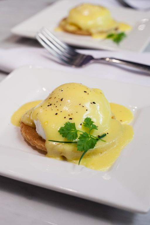 Eggs Benedict with Hollandaise Sauce on White Plates