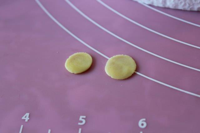 Two Small, Yellow, Flattened Modeling Chocolate Balls