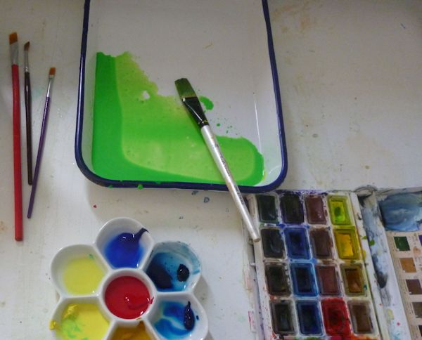 Watercolor pans and palette in process of mixing paints