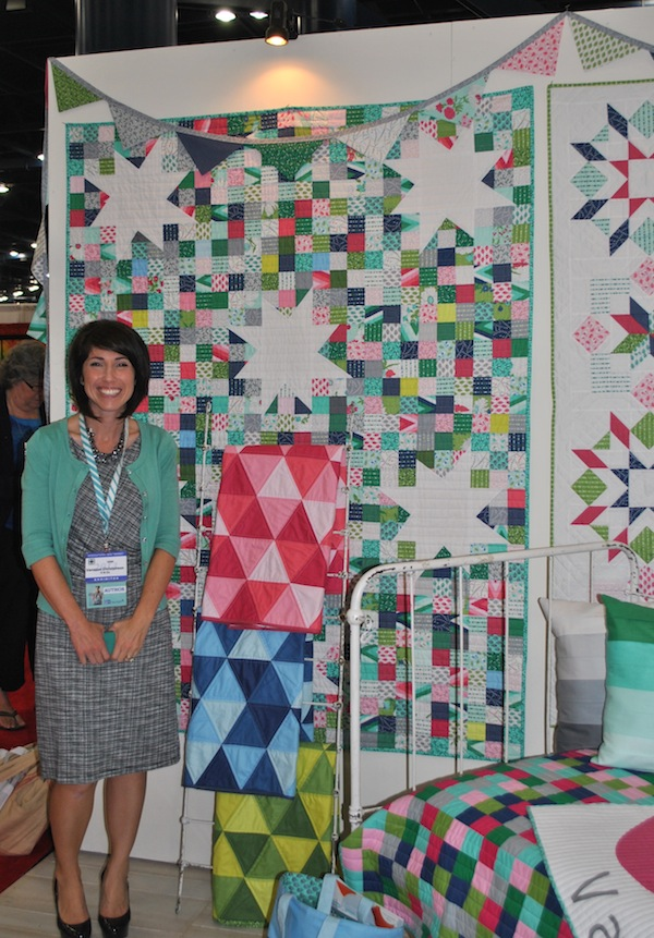Vanessa Christenson Smiling in Front of Beautiful Quilt