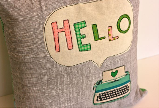 """Pillow Featuring Typewriter and """"Hello"""" Text"""