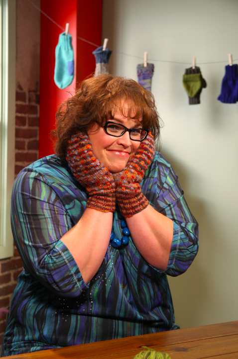 Marly Bird in Knit Gloves and Glasses, Smiling in Studio