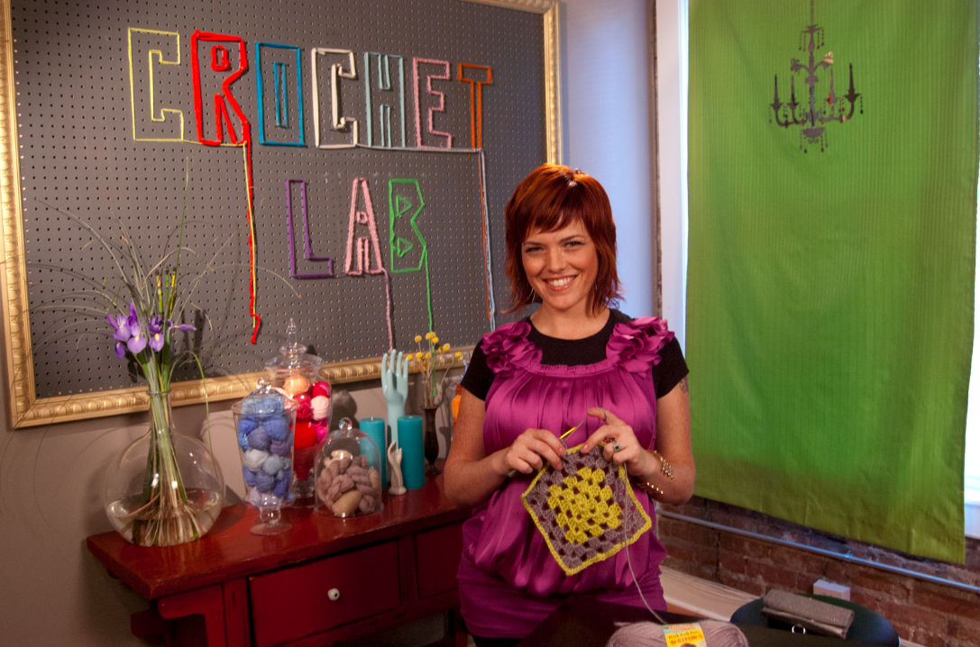 "Vickie Howell Holding Project, Standing in Front of ""Crochet Lab"" Board"