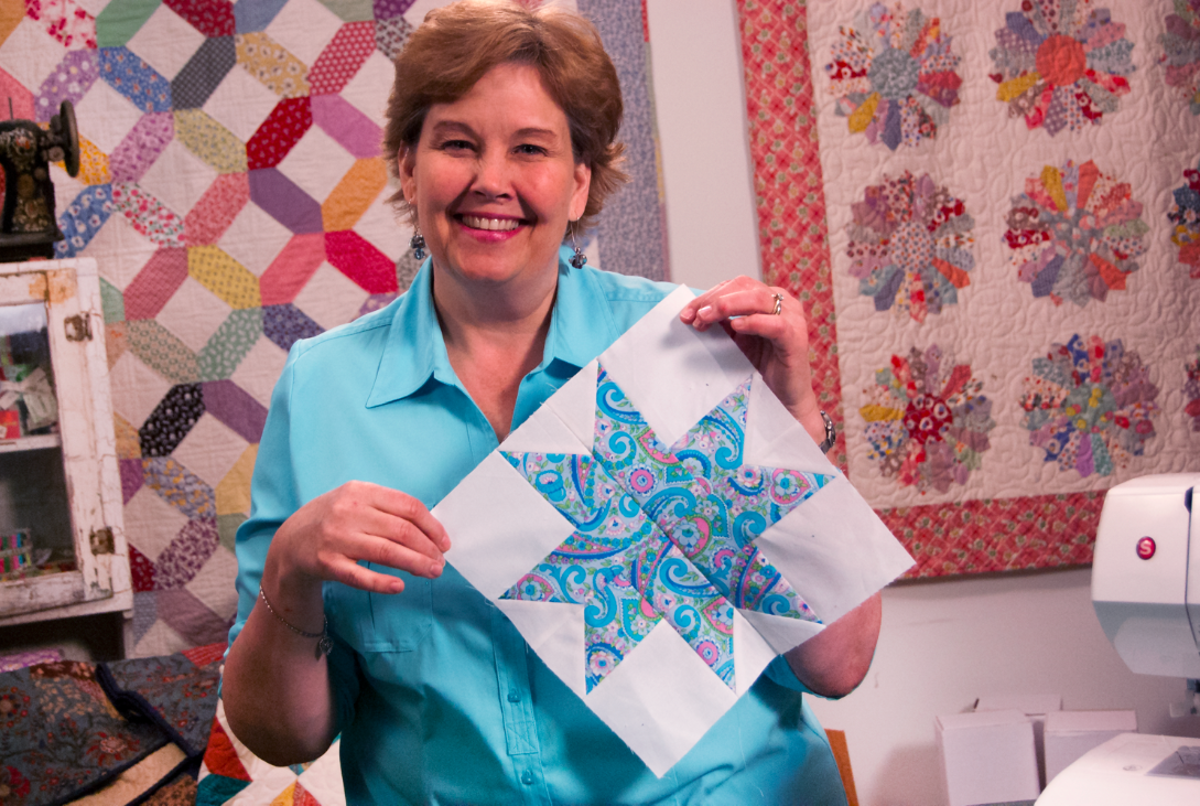Jenny Doan Holding Patterned Star Quilt Block in Quilting Studio
