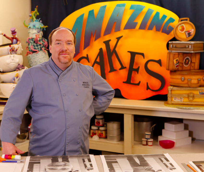 Mike McCarey Standing in Front of Sculpted Cakes