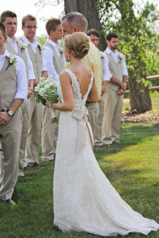 Bride in Wedding Dress Standing in Front of Groomsmen