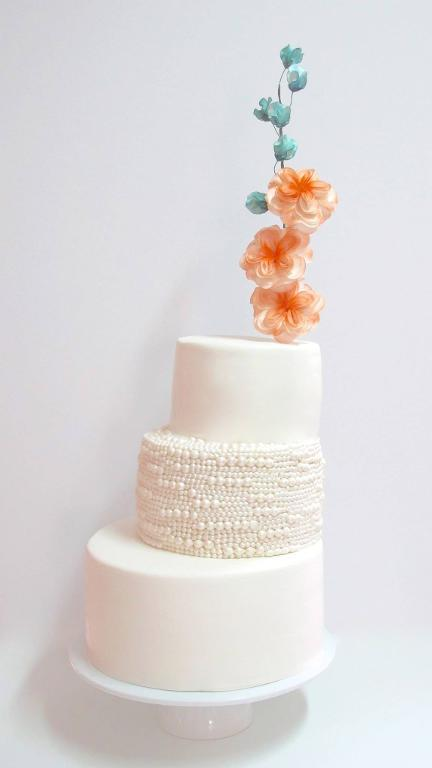 White Tiered Wedding Cake Topped with Fondant Floral Stem