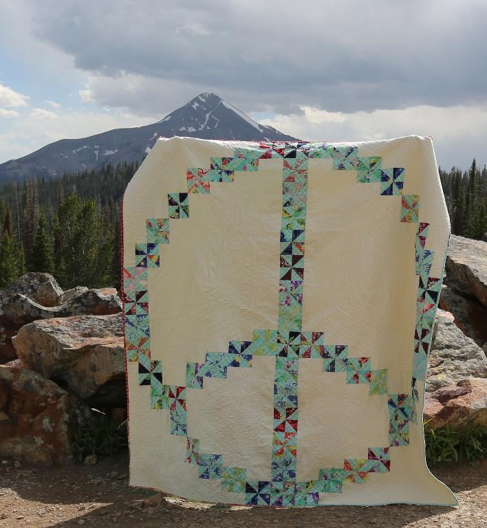 White Quilt Featuring Patterned Peace Sign
