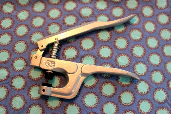 Metal Snap Pliers on Patterned Background