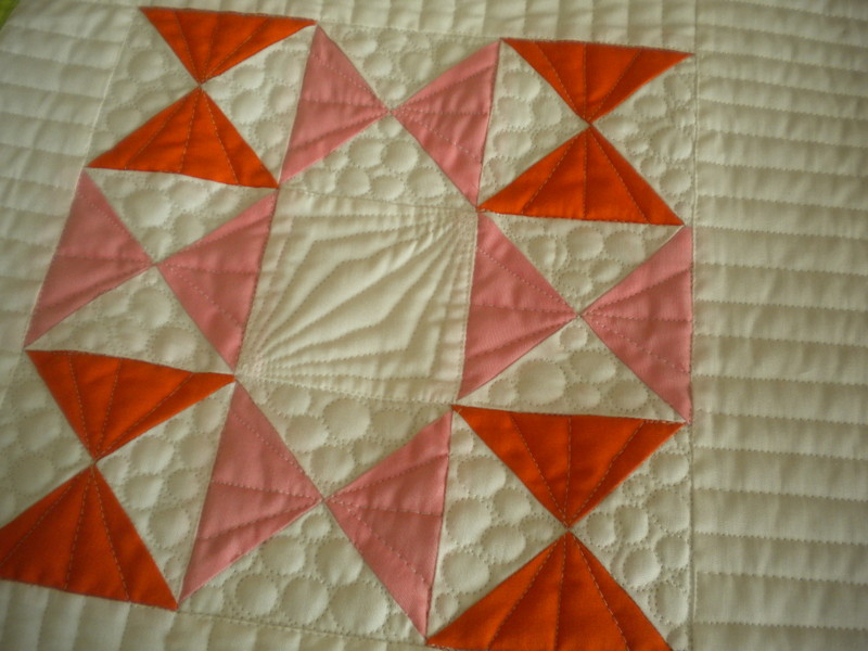 Quilt Featuring Red and Pink Quarter Square Triangles
