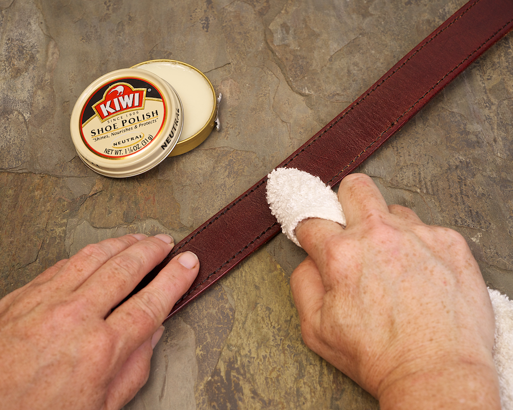 Treating belt, both face and back, is generally enough to get rid of any squeaking. Neutral shoe polish won't stain clothes and goes on easily with a soft cloth.