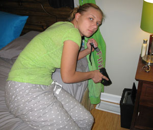 Girl removes essential items from her quick access safe in her room - Home Defense Training