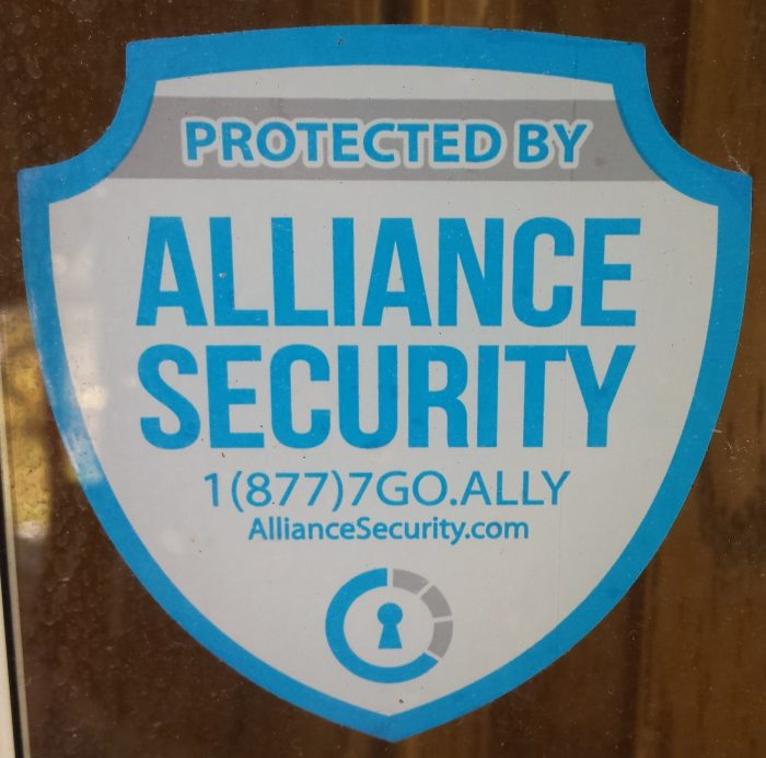 This window decal advertising that an alarm system is in use may help deter a burglar but does nothing to seriously protect you from a violent attack. Photo: author