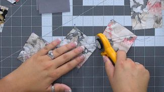 image of two hands using a round cutter to cut three pieces of fabric