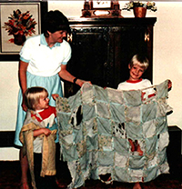 young and happy recipients of a quilt