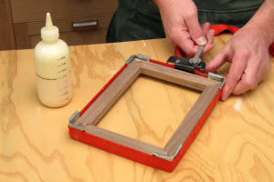 Assemble the mitered walnut frame. Use a band clamp or masking tape to hold the pieces together as the glue dries. Make sure the corners are tight and the frame is flat.
