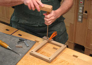 Chop the square holes using the chopping jog and a 3/8″ or 1/4″ wide chisel. Align, center, and square the chopping jig over each hole, then clamp it in place tight to keep it from shifting as you chop.