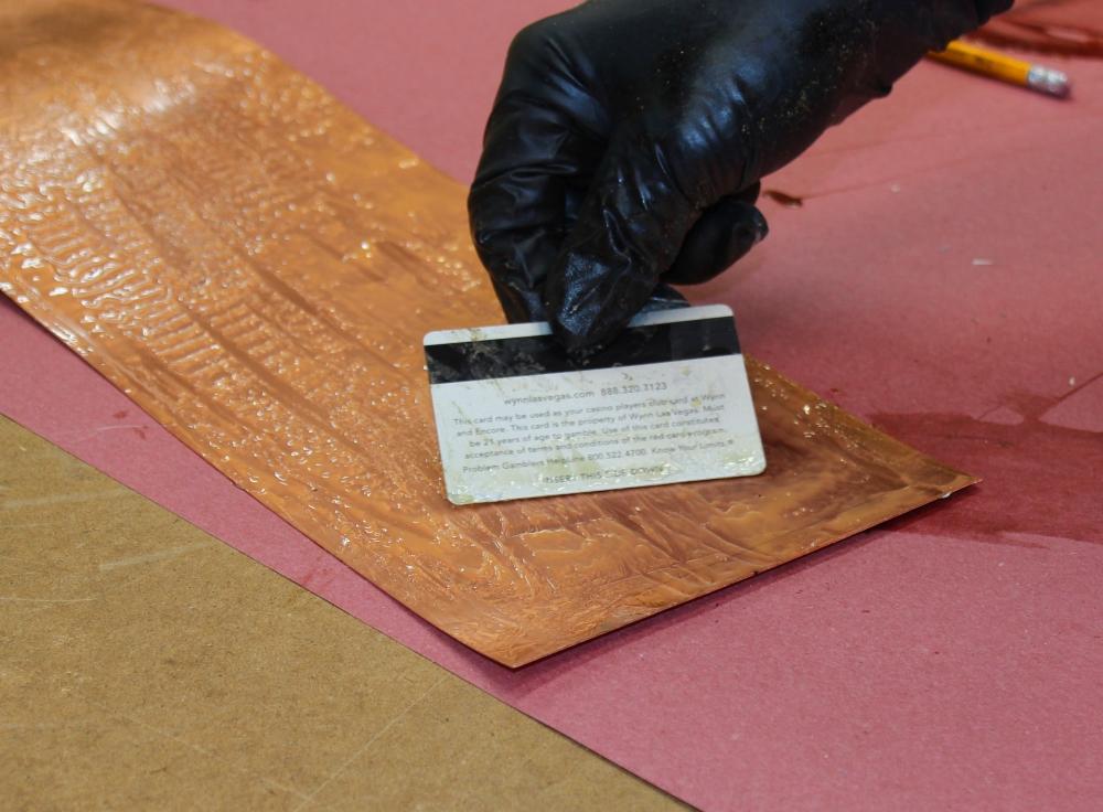 spreading glue on copper flashing
