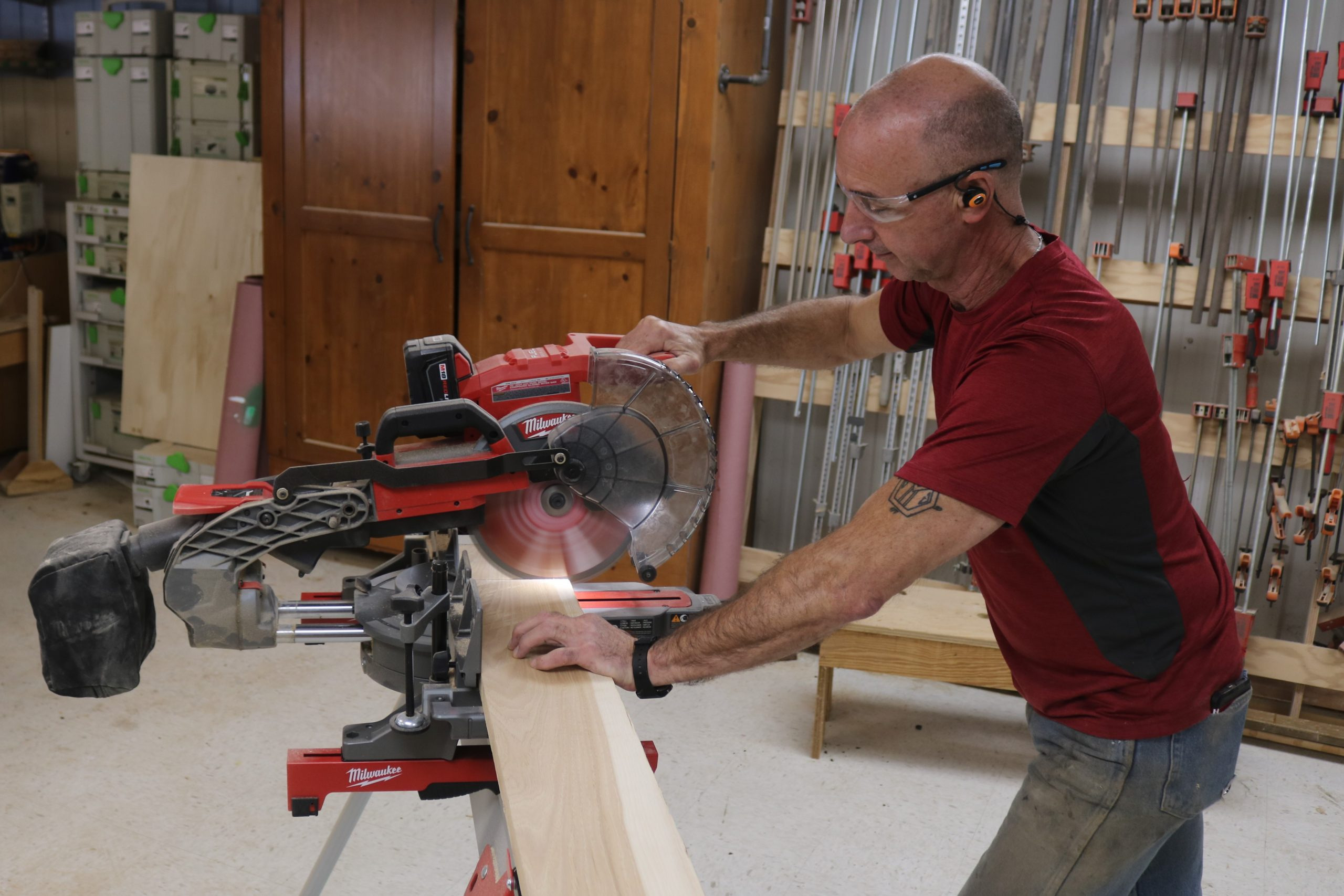 picture of a man using a cordless miter saw